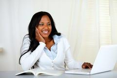 Donna bella dell'allievo che sorride e che osserva al computer portatile Immagini Stock Libere da Diritti
