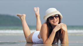 Donna bella giovane in occhiali da sole che si rilassano e che prendono il sole alla spiaggia tropicale video d archivio
