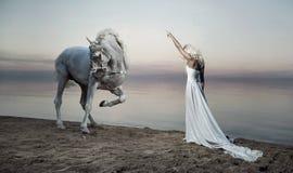 Donna ben fatto che sta di fronte al cavallo Immagini Stock Libere da Diritti