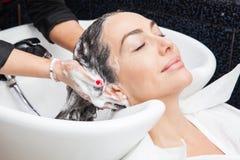 Donna bianca che ottiene un lavaggio dei capelli in un salone di bellezza Fotografia Stock