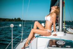 Donna in bikini bianco sull'yacht della barca di vendita immagine stock