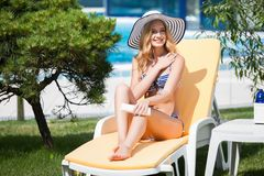 Donna in bikini che applica la crema del blocchetto del sole sul abbronzata immagini stock