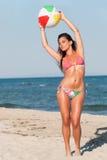 Donna in bikini che joying con il beach ball variopinto Immagini Stock
