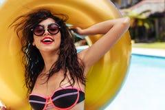 Donna in bikini che posa con l'anello gonfiabile vicino allo stagno immagine stock