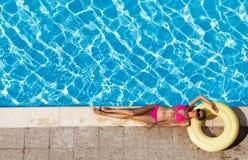 Donna in bikini che riposa sull'anello di gomma vicino allo stagno fotografia stock libera da diritti
