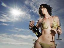 Donna in bikini che tiene Champagne Outdoors Immagine Stock
