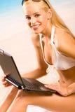 Donna in bikini con il computer portatile fotografie stock