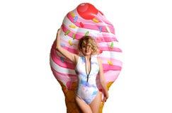 Donna in bikini con il gelato gonfiabile del materasso immagine stock