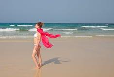 Donna in bikini e sciarpa rossa che cammina su una spiaggia Immagini Stock