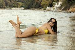 Donna in bikini giallo alla spiaggia fotografia stock libera da diritti