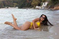 Donna in bikini giallo alla spiaggia immagine stock libera da diritti