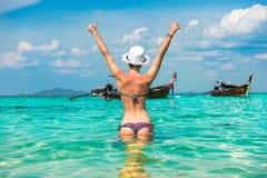 Donna in bikini luminoso che sta nell'acqua con i pollici su Immagine Stock