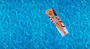 Donna in bikini sul materasso gonfiabile nella piscina immagine stock