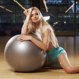 Donna bionda in abbigliamento di sport che posa con la palla d'argento di yoga Fotografie Stock Libere da Diritti