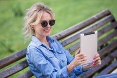 Donna bionda adorabile con la compressa elettronica in mani Fotografie Stock
