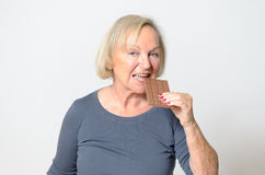 Donna bionda adulta che mangia cioccolato Antivari nella fine su Immagine Stock