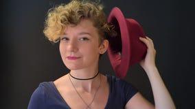 Donna bionda affascinante con capelli ricci che decolla il suo cappello e che copre il suo fronte, isolato su fondo nero archivi video