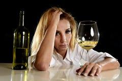 Donna bionda alcolica ubriaca da solo nei postumi di una sbornia di sofferenza beventi depressi sprecati di vetro di vino bianco Fotografia Stock Libera da Diritti