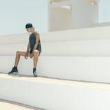 Donna bionda alla moda che si siede nello stadio stile urbano di modo Immagini Stock