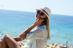 Donna bionda alla moda che sorride e che per mezzo dello smartphone Fotografia Stock