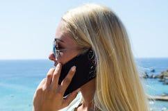 Donna bionda alla moda che sorride e che per mezzo dello smartphone Immagini Stock Libere da Diritti