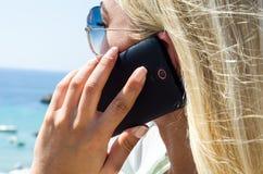 Donna bionda alla moda che sorride e che per mezzo dello smartphone Fotografia Stock Libera da Diritti