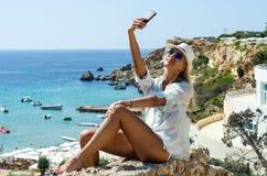 Donna bionda alla moda che sorride e che per mezzo dello smartphone Immagini Stock