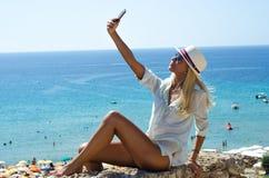 Donna bionda alla moda che sorride e che per mezzo dello smartphone Immagine Stock
