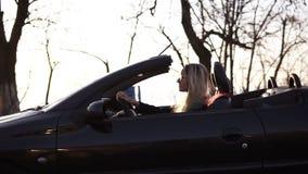 Donna bionda alla moda e giovane che conduce la sua bella automobile convertibile sportish nera Lato, metraggio del movimento len archivi video