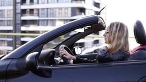 Donna bionda alla moda e giovane che conduce la sua bella automobile convertibile sportish nera Lato, metraggio del movimento len stock footage