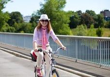 Donna bionda allegra che guida una bicicletta Immagini Stock Libere da Diritti