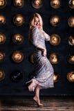 Donna bionda allegra felice in un vestito d'argento lungo su un fondo nero Celebrazione, partito, nuovo anno, compleanno immagini stock