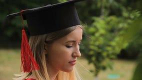 Donna bionda allegra in vestito accademico che controlla i messaggi sul telefono, graduazione stock footage