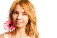 Donna bionda attraente che tiene un fiore fotografia stock