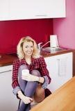 Donna bionda attraente in cucina. Fotografie Stock