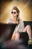 Donna bionda attraente e sexy con gli occhiali da sole che posano provocatorio seduta sulla sedia, fondo marrone chiaro Femmina s immagine stock