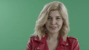 Donna bionda attraente in rivestimento rosso che posa contro lo schermo verde stock footage