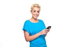 Donna bionda attraente Texting sul telefono delle cellule fotografia stock libera da diritti