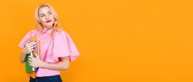 Donna bionda in blusa rosa con il mucchio dei libri Fotografie Stock