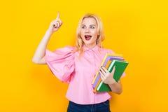 Donna bionda in blusa rosa con il mucchio dei libri Immagini Stock Libere da Diritti