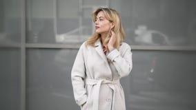 Donna bionda in camice che aspettano qualcuno nella via video d archivio