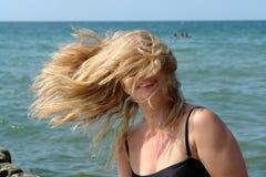 Donna bionda, capelli nell'aria, coprente il fronte. Fotografie Stock