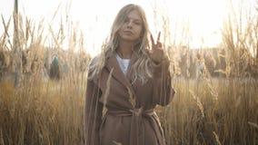 Donna bionda in cappotto che sta nel campo con alta erba e che esamina macchina fotografica video d archivio