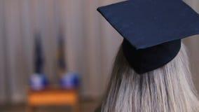 Donna bionda in cappuccio accademico, femmina pronta a ricevere il diploma di istruzione superiore archivi video