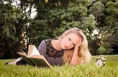 Donna bionda caucasica attraente che risiede nell'erba Immagine Stock