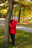 Donna bionda caucasica in cappotto rosso al parco di autunno che sta vicino alla a Immagine Stock