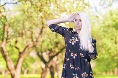 Donna bionda caucasica che posa contro Forest Outdoors verde Fotografia Stock