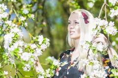 Donna bionda caucasica di rilassamento con capelli lunghi in parco vicino a fioritura Immagine Stock Libera da Diritti