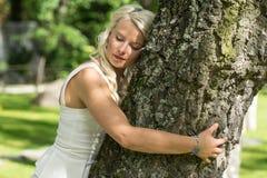 Donna bionda che abbraccia un albero in parco immagine stock
