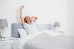 Donna bionda che allunga e che sbadiglia a letto di mattina Immagine Stock